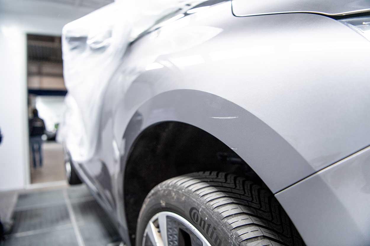 Griffe sur l'aile d'une voiture grise