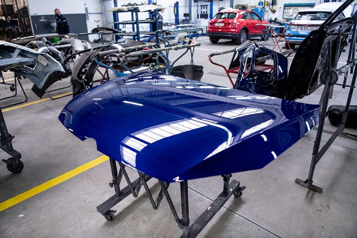 Gedemonteerde motorkap van een blauwe wagen
