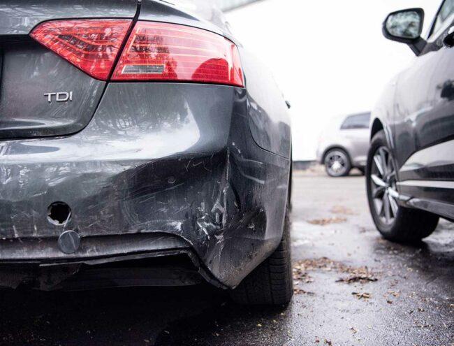 Coté droit du pare-chocs très abimé d'une voiture grise