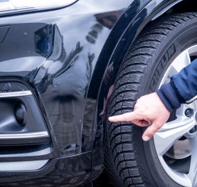 Man wijst naar de schade in de bumper van een donkere wagen