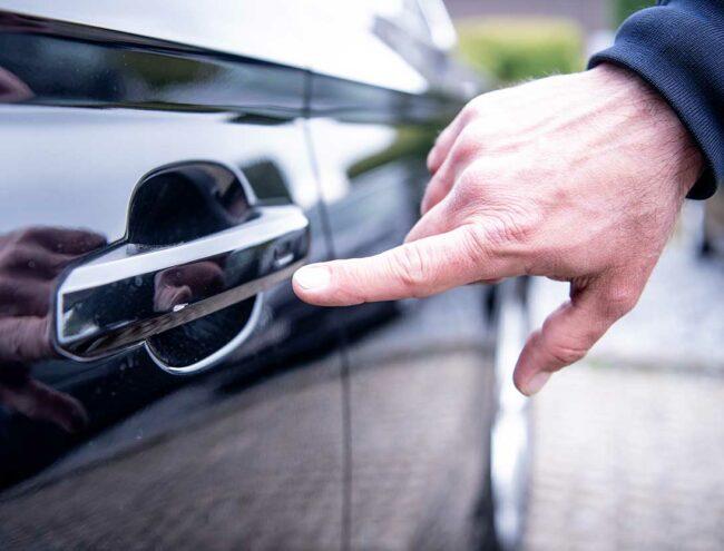 Main qui montre un éclat sur la poignée de la portière d'un voiture noire