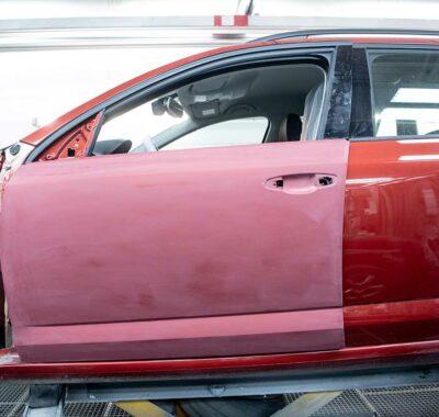 Foto van een rood deurpaneel klaar voor herstelling