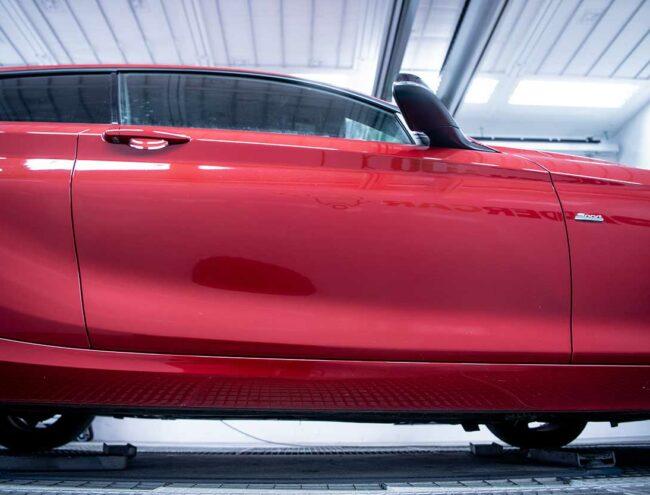 Portière d'une voiture rouge abimée en cours de réparation