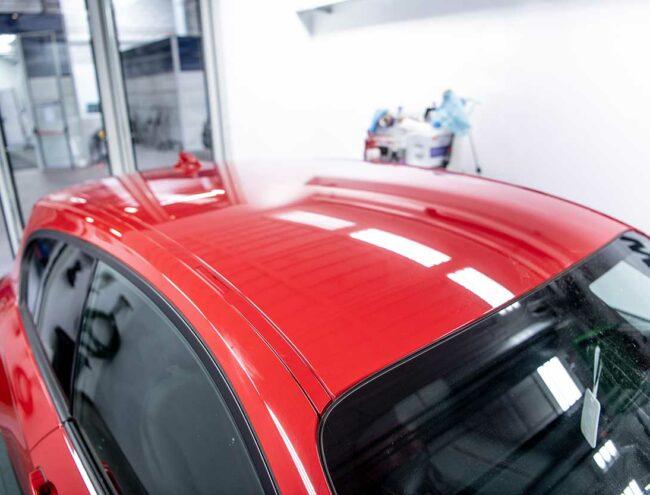 Toit d'une voiture rouge en cours de réparation dans la Smart box