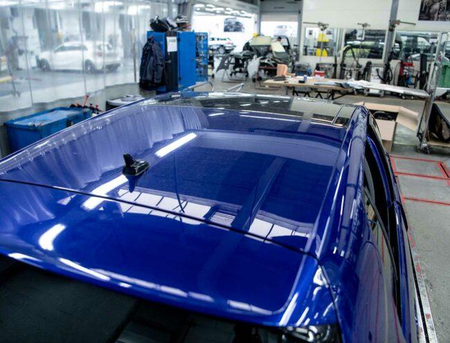 Toit d'une voiture bleue éléctrique en cours de réparation