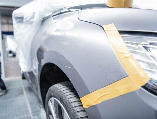 Réparation d'une griffe en cours sur une voiture grise