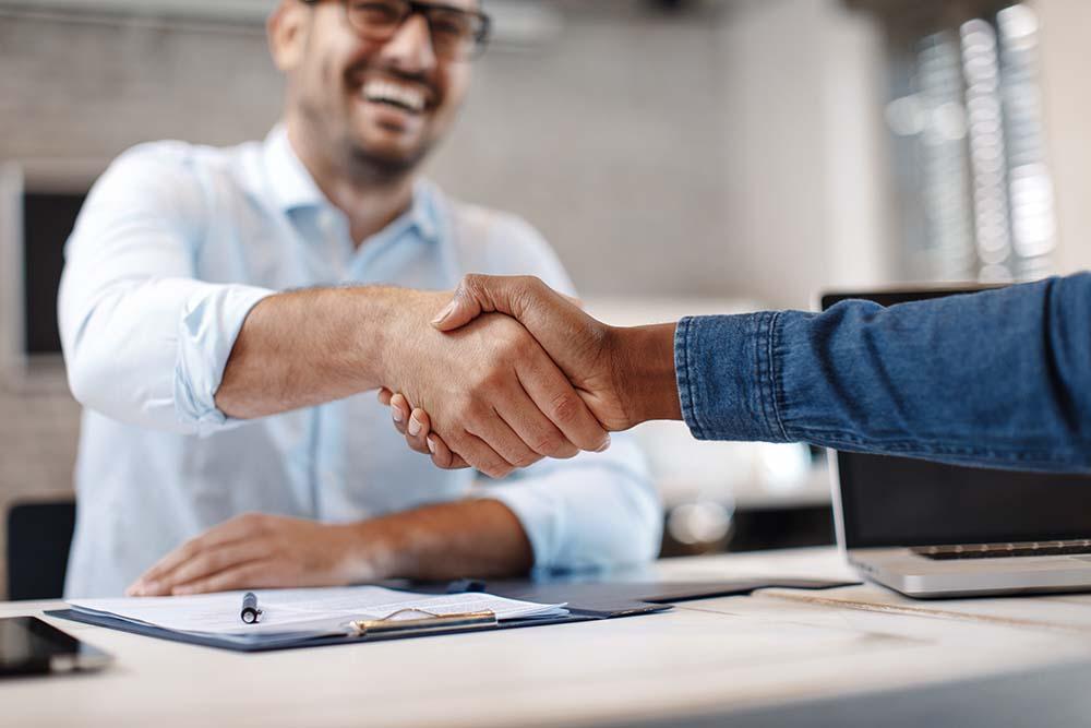 Foto van twee personen die elkaar een hand geven