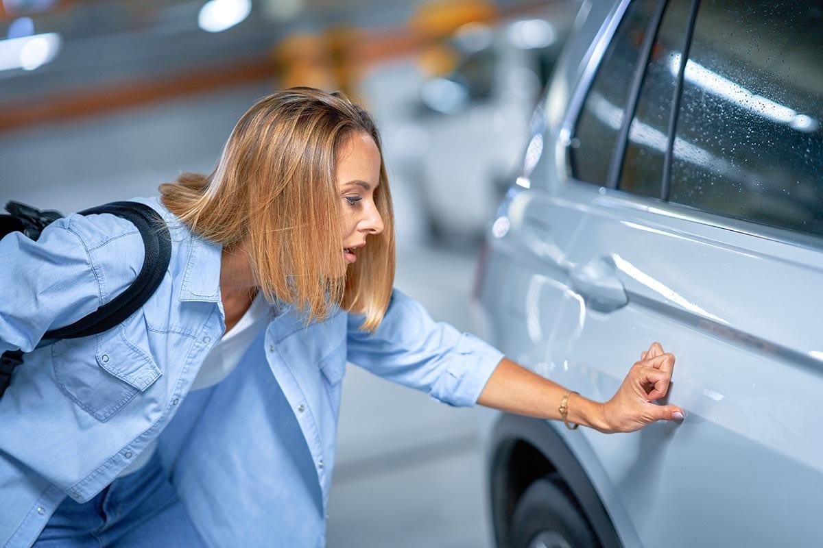 Blonde vrouw die de schade aan haar wagen bekijkt