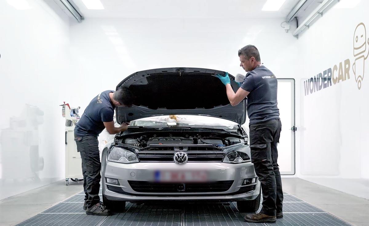 Twee medewerkers van Wondercar die een auto aan het demonteren zijn